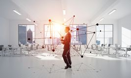 Networking and social communication concept as effective point for modern business. Elegant businessman in modern office interior and social connection concept Stock Photo