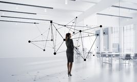 Networking and social communication concept as effective point for modern business. Elegant businesswoman in modern office interior and social connection concept Royalty Free Stock Images