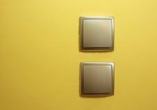 Netzschalter des flachen Silbers zwei, einer unter dem anderen auf dem Gelb Lizenzfreies Stockfoto
