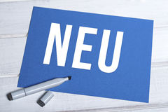 Neu blue board with german writing. Blue board with german word neu written in white and black marker lying on top Royalty Free Stock Photo