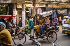 Neu-Delhi, Indien - 16. April 2016: Rikschareiter transportiert Passagier am 16. April 2016 in Neu-Delhi, Indien Fahrradrikschas Lizenzfreies Stockfoto