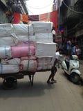 NEU-DELHI, INDIEN, im September 2016 - bemannen Sie tragende schwere Last auf den Straßen Stockfoto
