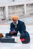 Neu-Delhi - März 2011 - Sikhemigrant, sitzend auf der Pflasterung, Studien, wie man erlaubterweise in die USA kommt. Lizenzfreie Stockbilder