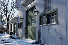 Neu-England weiße Scheune nach einem Schneesturm mit grünen Türen und grüner Ordnung Lizenzfreies Stockfoto