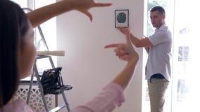 Neu streichend, hängt schöner Mann Bild auf Wand, während Frau Rahmen mit dem Finger macht und entscheidet auf Dekoration auf Wän stock video
