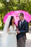 Neu-verheiratete Paare unter einem rosafarbenen Regenschirm Lizenzfreie Stockfotos