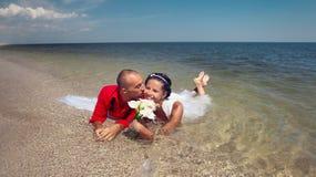Neu-verheiratete Paarschwimmen im Meer Lizenzfreies Stockbild