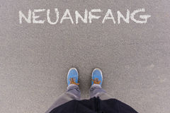 Neuanfang, German text for New Beginning text on asphalt ground, Royalty Free Stock Photography
