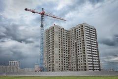 Neubauwohnungen auf der Baustelle mit einem industriellen Kran Lizenzfreie Stockfotografie