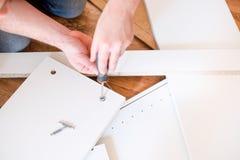 Neue Ausgangs- und des Manneszusammenbauende Möbel es sich tun stockbilder