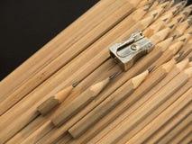 Neue Bleistifte und drei alt, die verwendete mit Metallbleistiftspitzer Stockbild
