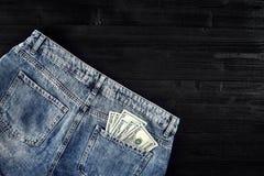 Neue Dollarrolle in der Hüftetasche der abgenutzten Blue Jeansnahaufnahme Dollar in der Gesäßtasche abgenutzten Blue Jeans Nahauf Lizenzfreie Stockfotografie