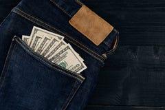 Neue Dollarrolle in der Hüftetasche der abgenutzten Blue Jeansnahaufnahme Dollar in der Gesäßtasche abgenutzten Blue Jeans Nahauf Stockfotografie