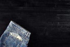 Neue Dollarrolle in der Hüftetasche der abgenutzten Blue Jeansnahaufnahme Dollar in der Gesäßtasche abgenutzten Blue Jeans Nahauf Stockbilder