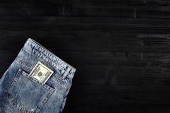 Neue Dollarrolle in der Hüftetasche der abgenutzten Blue Jeansnahaufnahme Dollar in der Gesäßtasche abgenutzten Blue Jeans Nahauf Lizenzfreies Stockbild