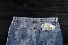 Neue Dollarrolle in der Hüftetasche der abgenutzten Blue Jeansnahaufnahme Dollar in der Gesäßtasche abgenutzten Blue Jeans Nahauf Lizenzfreie Stockbilder