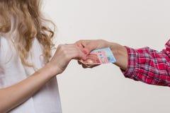 Neue Dollarrolle in der Hüftetasche der abgenutzten Blue Jeansnahaufnahme Mutter gibt dem Kind ein Bargeld stockbild