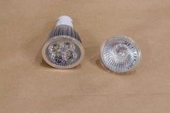 Neue geführte Birne und die alte Halogenlampe auf Kraftpapier Stockfotos