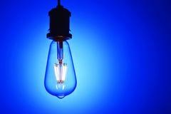 Neue geführte Glühlampe über blauem Hintergrund Lizenzfreies Stockbild