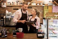 Neue Geschäftseigentümer im Café unter Verwendung der Tablette stockbilder