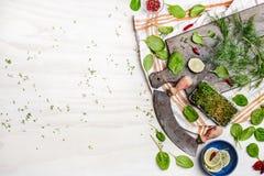 Neue Grüns und Gewürzbestandteile mit Zitrone und Gewürzen auf rustikalem Schneidebrett mit Krautzerhacker auf weißem hölzernem H Stockfotografie