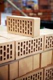 Neue hohle Ziegelsteine gestapelt am Lager für Verkauf Viele von Lehmziegelsteinnahaufnahme Stockfotografie