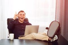 Neue Idee, entspannter Mann, der Projekt mit den Beinen auf Schreibtisch macht Stockfotos