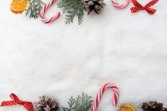 neue Ideen, das Haus zu verzieren dieses Weihnachten Niederlassungsbaum, -kegel und -süßigkeit auf Schnee Draufsicht, flache Lage lizenzfreie stockbilder