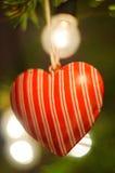 neue Ideen, das Haus zu verzieren dieses Weihnachten Rotes Herz, das an Weihnachtsbaum hängt leuchten Hintergrund Bokeh Lizenzfreie Stockfotos
