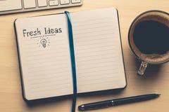 Neue Ideen - Wörter auf offenem Notizbuch auf Holztisch mit Tasse Kaffee, Draufsicht Spornen Sie und Kreativitäts-Konzept an Stockfoto