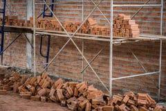 Neue Innenwand des roten Backsteins mit dem Baugerüst im Bau Lizenzfreies Stockfoto