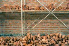 Neue Innenwand des roten Backsteins mit dem Baugerüst im Bau Stockbild