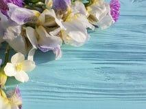 Neue Irisblütenschönheit feiern rustikale dekorative Karteneleganzblume auf einem blauen hölzernen Hintergrund Stockbilder