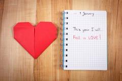 Neue Jahre Beschlüsse geschrieben in Notizbuch und in rotes Papierherz Lizenzfreies Stockfoto