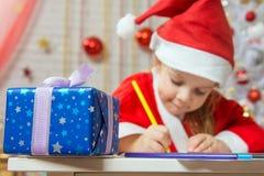 Neue Jahre Geschenk im Vordergrund, im Hintergrund Mädchen zeichnet Bleistift Stockfoto