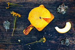 Neue Kantalupenmelonenscheiben auf einem dunklen Hintergrund mit Blume und mose Flache Lageansicht des Landlebens Stockfotos