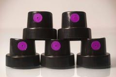 Neue Kappen von der Dosenaerosolfarbe für die Graffiti, die in Form eines Pyramidennahaufnahme-Weißhintergrundes stehen stockfoto