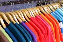 Neue Kleidung bunt in einem Shopspeicher lizenzfreies stockbild