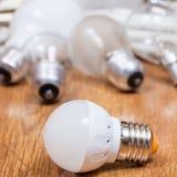 Neue LED-Lampe und benutzte Birnen auf Tabelle Lizenzfreie Stockfotos
