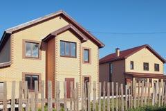 Neue nicht bevölkerte Landhäuser hinter einem alten Zaun Lizenzfreies Stockfoto