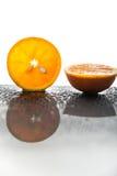 Neue orange Scheibe mit Hälfte Tropfen einer Orange und des Wassers Stockbilder