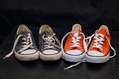 Neue orange und alte blaue Turnschuhe Stockfoto