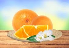 Neue Orange und Scheiben mit Blumen auf Platte auf Natur Stockfoto