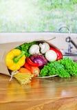 Neue organische Lebensmittellieferung des rohen Gemüses in der Papiertüte auf Holzbank stockfoto
