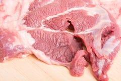 Neue rohe Rindfleischfleischscheiben auf hölzernem Stockfotos