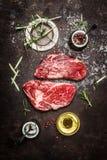 Neue rohes Fleisch Ribeye-Steakvorbereitung mit Kräutern, Gewürzen und Öl auf dunklem rustikalem Metallhintergrund Lizenzfreie Stockfotografie