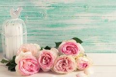 Neue rosa Rosen und Kerze im Vogelkäfig Lizenzfreies Stockfoto