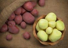 Neue rote rohe ganze und abgezogene Kartoffeln Stockbild
