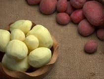 Neue rote rohe ganze und abgezogene Kartoffeln Lizenzfreie Stockbilder