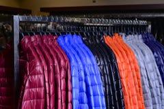 Neue Sammlung unten Jacken auf Aufhängern im Markt Lizenzfreies Stockfoto